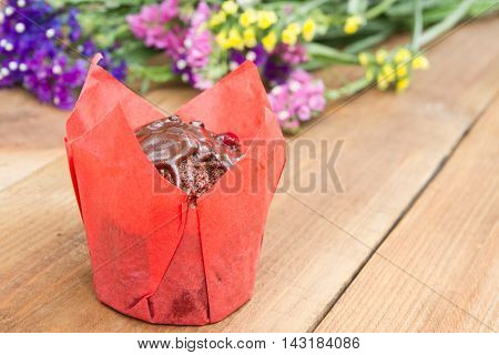 delicious chocolate muffin individually wrapped on wooden background