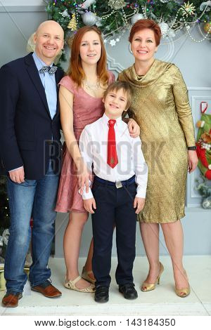 Mother, father and two children pose in room with christmas decoration