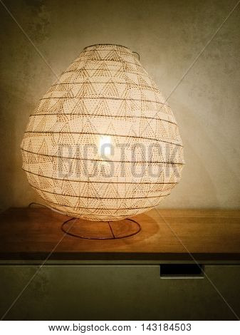 Vintage style photo of a lantern on a dresser.