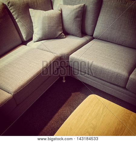 Gray corner sofa with cushions and wooden coffee table.