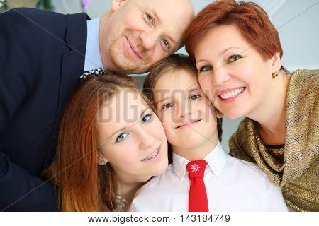 Happy beautiful mother, father and two children pose in room, close up