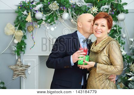 Happy husband and wife with gifts, man kisses woman in room with christmas decoration