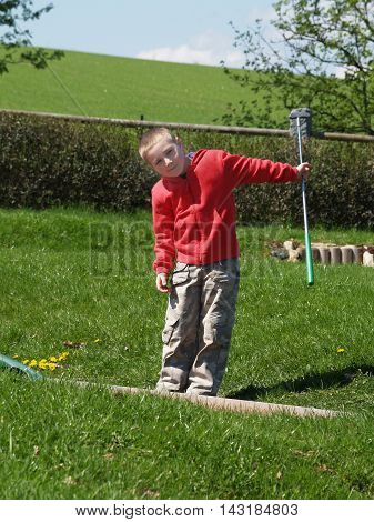 Little boy after playing golf on vacation