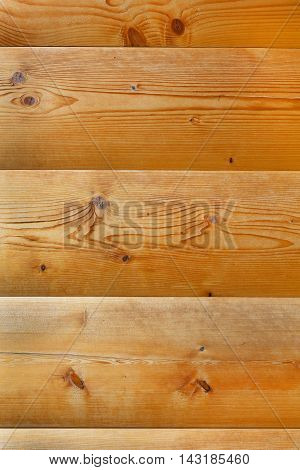 Bright amber-colored wood wall. Freshly planed pine logs with knots. Background texture planks.