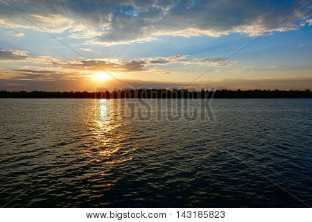 Orange setting sun over water surface with ripples and tree tops on far coast
