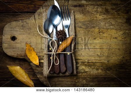 Autumn Halloween Thanksgiving composition. Autumn rustic set of cutlery knife, spoon, fork, tea spoon on rustic cutting board wtih autumn yellow leaves. Copy space. Top view