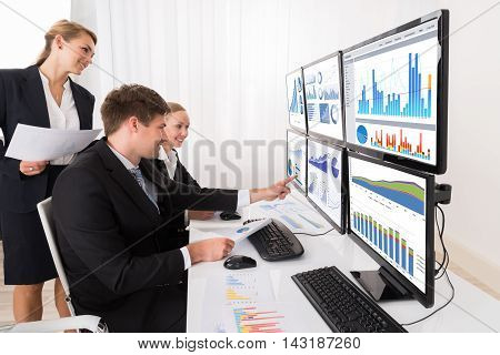 Happy Young Businesspeople Analyzing Graphs On Multiple Computers In Office
