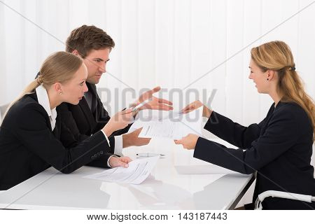 Unhappy Female Colleague Showing Document To Young Businesspeople In Meeting
