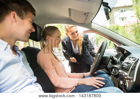 Young Happy Female Saleswoman Showing New Car To Couple