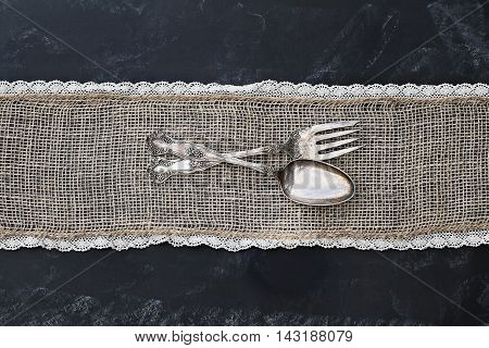 Antique silverware spoon and fork over a rustic blackboard background with burlap and lace. Image shot from overhead.