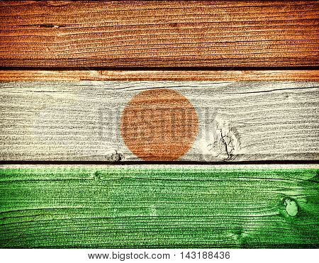 Flag of Niger painted on old grungy wooden background: 3d illustration