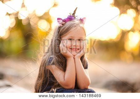 Smiling kid girl 4-5 year old wearing unicorn headband over nature background. Looking at camera. Childhood. Summer portrait over sunset. Selective focus.