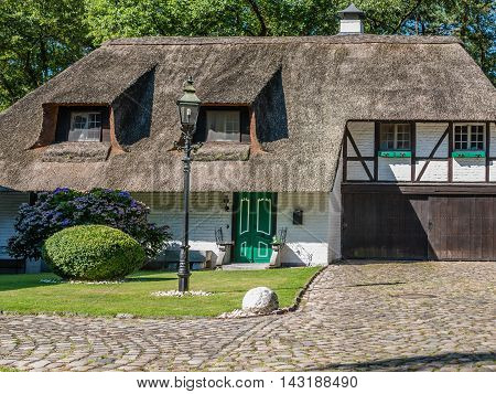 Cottage house with thatched roof and a paved yard