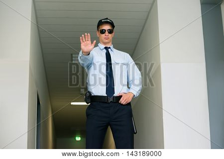 Young Male Security Guard Making Stop Gesture At The Entrance
