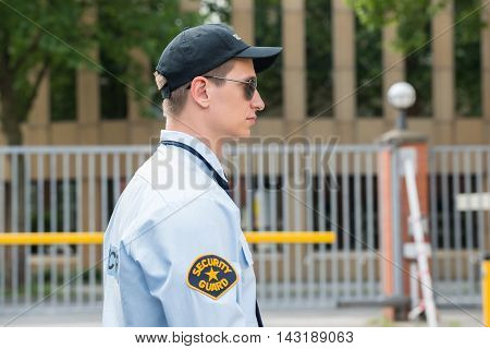 Side View Of A Young Male Security Guard In Uniform