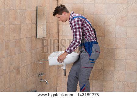 Side View Of Happy Male Plumber Installing Sink In Bathroom