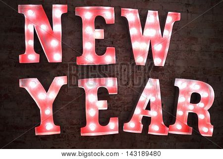 Big red letters with lamps - New Year - on brick wall at night