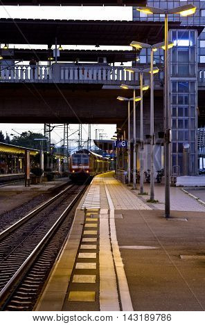 View of railroad platform at night. Train waiting for passenger at station. Passengers expect arrival of the train on the platform of the Central station.Train track railway station platform. Friburg Germany.