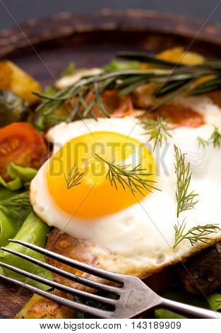 Closeup fried egg and vegetables with old fork
