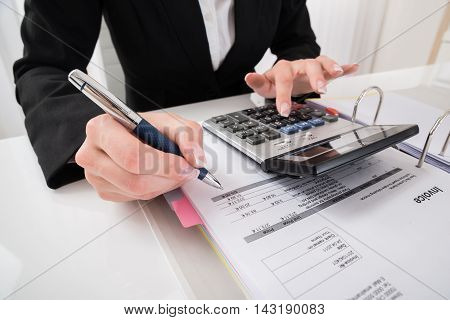 Close-up Of Businesswoman Hand Calculating Business Report At Desk