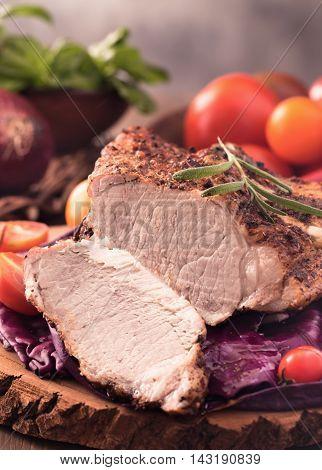 Cut roast pork steak and vegetables closeup