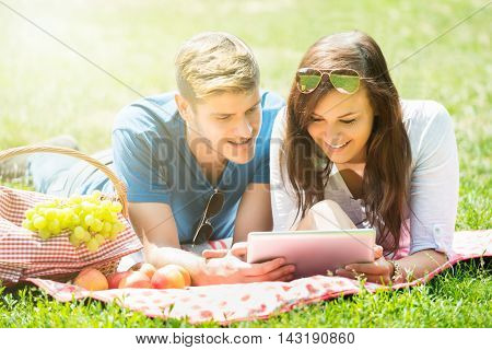 Happy Couple Using Digital Tablet While Lying In Park