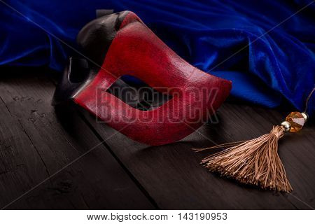 Decorated mask for masquerade and blue velvet on wooden surface