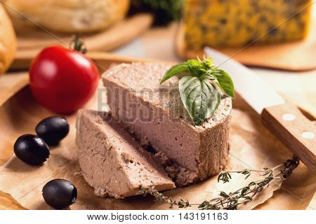 Duck pate on plate with basil and knife
