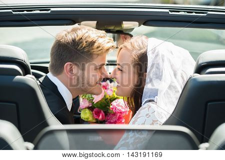 Newlyweds Young Smiling Couple Kissing In The Wedding Car