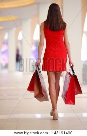 Beautiful girl in dress goes with bags in shopping center, back view
