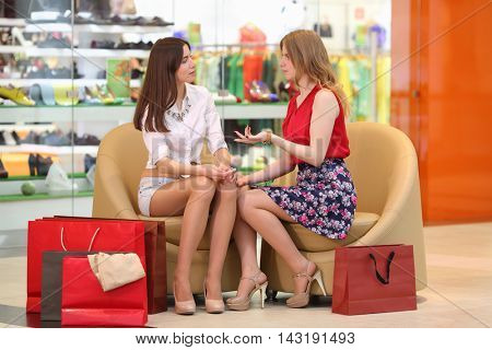 Two girls sit in leather armchairs with bags and talk in big modern mall