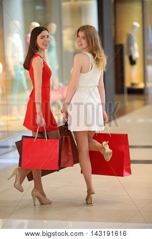 Two beautiful girls with bags stand near showcase with mannequins
