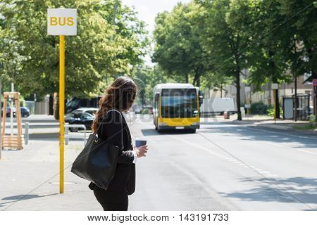 Young Businesswoman With Disposal Cup Waiting For Bus