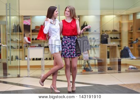 Two pretty girls with bags embrace and smile in big modern mall