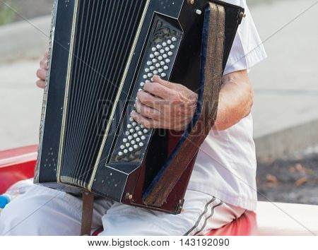 Human hand playing the accordion close up