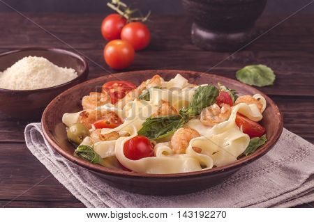 Fettuccine pasta with shrimp, tomatoes and basil on rustic wooden table