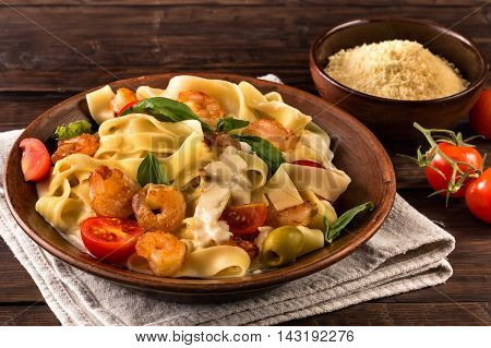 Fettuccine pasta with shrimp, tomatoes and basil on old wooden table. Rustic style