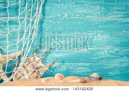 Fishing net and sea shells on sand on blue wooden background