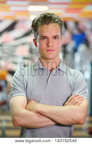 Young handsome man smiles, crosses his arms in modern fitness club