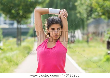 Sporty Young Woman Doing Morning Exercise In Park