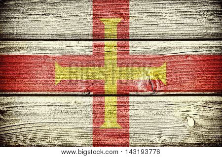 Flag of Guernsey painted on old grungy wooden background: 3d illustration