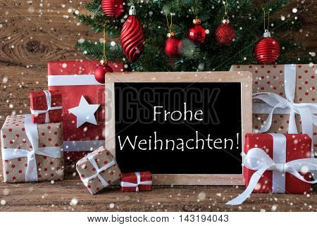 Colorful Card For Seasons Greetings. Christmas Tree With Balls And Snowflakes. Gifts Or Presents In The Front Of Wooden Background. Chalkboard With German Text Frohe Weihnachten Means Merry Christmas