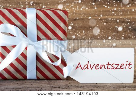 Christmas Gift Or Present On Wooden Background With Snowflakes. Card For Seasons Greetings. White Ribbon With Bow. German Text Advetszeit Means Advent Season