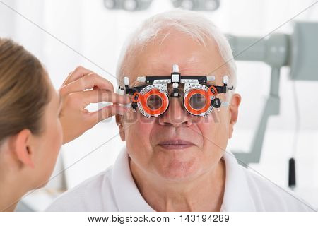 Close-up Of An Optometrist Checking Senior Male Patient Vision With Trial Frame At Eye Clinic