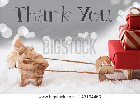 Moose Is Drawing A Sled With Red Gifts Or Presents In Snow. Christmas Card For Seasons Greetings. Silver Background With Bokeh Effect. English Text Thank You