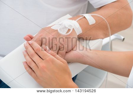 Close-up Of A Doctor Holding Patient's Hand With Iv Drip