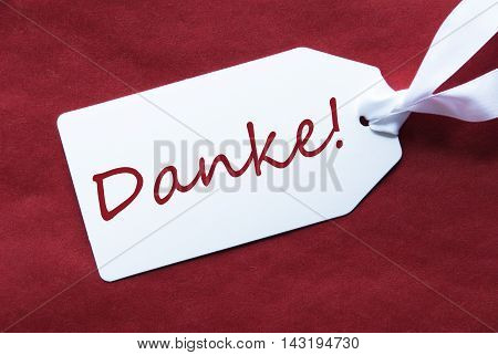 One White Label On A Red Textured Background. Tag With Ribbon. German Text Danke Means Thank You