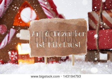 Gingerbread House In Snowy Scenery As Christmas Decoration. Sleigh With Christmas Gifts Or Presents And Snowflakes. Label With German Text Am 6. Dezember Ist Nikolaus Means Nicholas Day