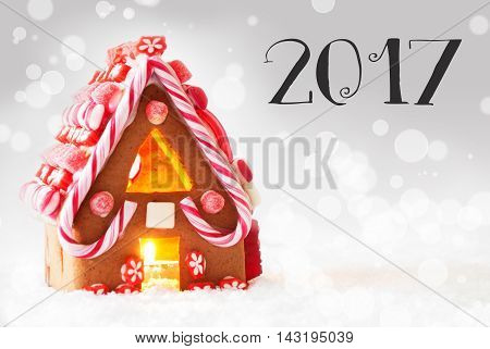 Gingerbread House In Snowy Scenery As Christmas Decoration. Candlelight For Romantic Atmosphere. Silver Background With Bokeh Effect. English Text 2017 For Happy New Year