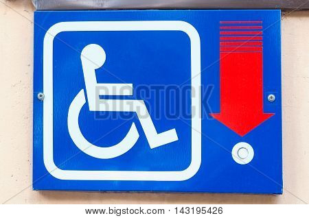 Metal tablet with signal button for the disabled people on the building wall with red pointer showing the button